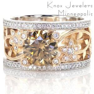 This custom two tone engagement ring is a real statement piece. The hints of yellow in the champagne colored center diamond are complimented by the 14k yellow gold vine and floral pattern. This organic design is framed on either edge by a 14k white gold band set with white diamonds.