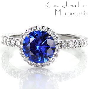 This stunning engagement ring catches the eye with an elegant cobalt blue sapphire center stone. Round brilliant diamonds are set into the underside of the halo to ensure that the piece will catch the light from every angle. The classic diamond band compliments the setting and highlights the center stone.