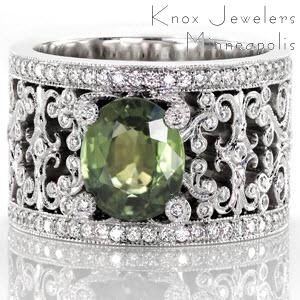 This beautiful custom engagement ring features a 2.50 carat oval cut green sapphire center. The rich, earthy green is highlighted by the intricate curls of white gold that form the pattern of the band. The curls of the filigree pattern, and of the center prongs, are bezel set with brilliant diamonds.