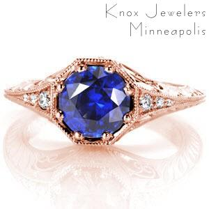 Henderson custom antique inspired engagement ring with a knife edge band and octagonal central bezel holding a round blue sapphire.