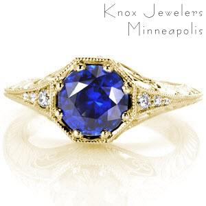 St Louis custom antique inspired engagement ring with a knife edge band and octagonal central bezel holding a round blue sapphire.