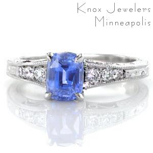 A vibrant blue cushion cut sapphire center stands out in this custom, antique inspired engagement ring. The band flares as it reaches the center and is adorned with round diamonds that graduate in size. The top and sides of the band are detailed with hand engraved scroll designs, and hand formed filigree curls.