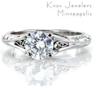 Custom engagement ring in Montreal with a hand engraved knife edge band and filigree curls bordering the center diamond.