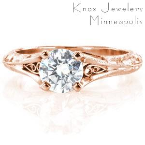 Custom engagement ring in Victoria with a hand engraved knife edge band and filigree curls bordering the center diamond.