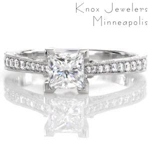 The Princess Vera is an exquisite antique inspired design that features a 0.75 carat princess cut in chevron prongs. Hand engraving, filigree, and milgrain adorn the sides of the ring for a vintage appeal. Micro pavé diamonds graduate in size along the band, giving brilliance and shine to the white gold metal.