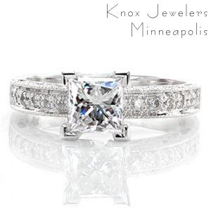 The Adorable Princess is a darling design with a 1.00 carat princess cut diamond. The top of the band is accented by large, bead-set stones. The sides feature bezel set diamonds and cut outs, including a heart shape on the side of the center stone. Milgrain detail adds texture to the edges.