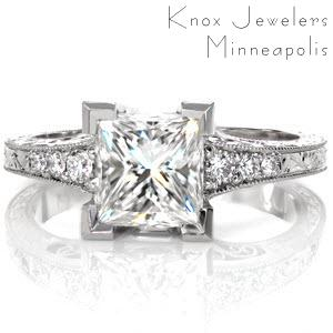 Design 2885 joins the vintage styling of engraving and hand crafted filigree with a stunning 1.50 carat Princess cut diamond. Chevron prongs create the most secure setting and the flared band is accented by graduated round cut diamonds. Hand applied milgrain and detailed under gallery add the perfect finishing touch.