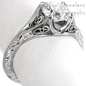 Filigree engagement ring in Regina with round brilliant center stone and engraved band.