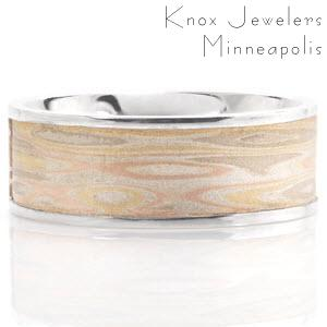 A dashing design, this comfort fit ring is inlayed with a hand made Mokume Gane piece. This Mokume Gane pattern is created using all three colors of gold, with a silver binding layer in between each one. The billet of layered metals is manipulated so that when it is flat it will be reminiscent of ripples on water.