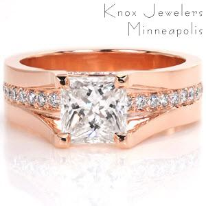 This cathedral style engagement ring is a regal custom design. The 1.25ct princess cut center diamond is set high enough so a row of bead set round diamonds can go completely under the center stone. More small diamonds adorn the sides of the band between the prongs for added effect. This ring is shown in 14k rose gold.