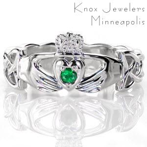 Crafted in 14k white gold, our Claddagh ring joins a trinity of Celtic heritage. A round cut natural emerald is captured by the heart. Two reaching hands represent friendship and the milgrain adorned crown represent loyalty. With a high polish finish, the woven Celtic knot band is pierced near the hands.
