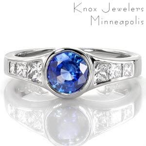 The 1.00 carat vivid blue sapphire is fashioned in a white gold bezel putting emphasis on the cobalt hue of the center stone. Princess cut side stones graduate in size drawing the eye to the beautiful sapphire center. The high polished metal gives this contemporary design a very sleek appearance.