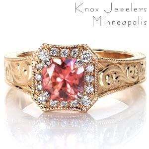 This stunning custom design features a rare colored sapphire center. The rich, fiery colors of the sapphire are accentuated by the warm tones of the yellow gold band. A uniquely shaped halo is bead-set with vibrant diamonds. The wide ring is detailed with gorgeous hand engraved designs and hand formed filigree curls.