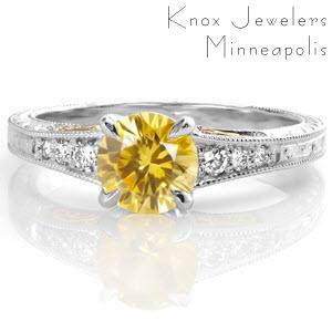 The round 1.00 carat yellow sapphire is a striking pop of color in this white gold setting. Hand wrought yellow gold filigree curls compliment the vivid hue of the sapphire center.  Micro pavé diamonds, hand engraving, and milgrain adorn this antique inspired design for a vintage appeal.