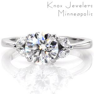 New Orleans custom engagement ring with marquise side diamonds and a round brilliant center stone.