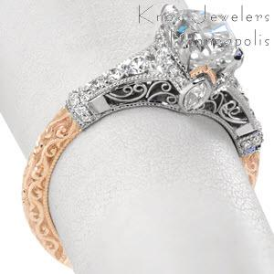 Stunning cushion cut antique engagement ring style in Raleigh. This unique engagement ring features a rose gold lower band with a white gold upper band. The rose gold is exquisitely details with hand carved relief engraving. The upper section of the piece is detailed with hand formed filigree curls and micro pave diamonds.