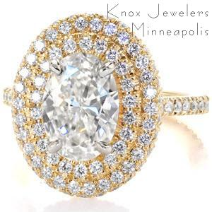 Design 3004 is a statement ring that boldly displays a 2.00 carat Oval cut diamond.  Meticulous placed within unique U-Cut prongs and bead set, a halo of two rows are completely adorned with round cut diamonds.  Crafted in 14k yellow gold, the band also has U-Cut prongs and an open gallery.