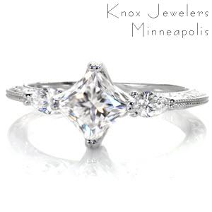 This elegant three stone diamond engagement ring is breathtaking with a kite-set princess cut center diamond. The antique inspired knife edge band flows beautifully down from the points of the pear cut side stones. This unique engagement ring is exquisitely detailed with relief-style hand engraving and milgrain.