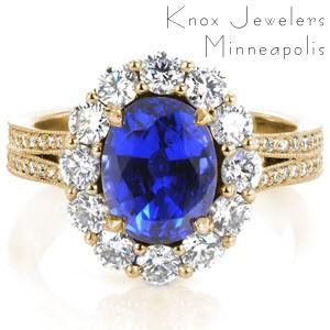 Phoenix custom engagement ting with an oval blue sapphire surrounded by a diamond halo on a split shank band