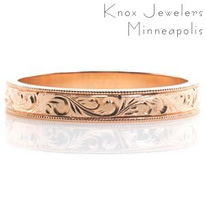 This antique inspired wedding band is handcrafted in 14k rose gold. Hand engraved scroll patterns extend along the entire band for a continuous look. Milgrain texture is applied to the edges of the design to add dimension and complete its vintage appeal.