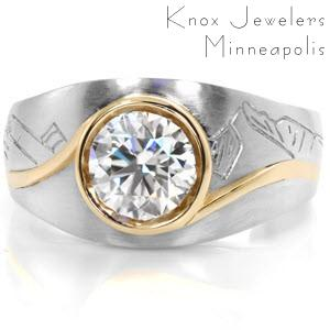This custom design is crafted in two-tone platinum and 18K yellow gold.  It features picturesque hand engraving of a mountainous skyline framing the central gemstone.  A 1.00 carat round brilliant diamond is accented by a curving full bezel in a contrasting vivid yellow gold.
