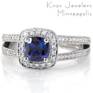 Cielito Sapphire displays a royal blue 1.00 carat cushion cut sapphire in a four prong halo setting. Round diamonds outline the sapphire to embellish the beautiful blue of the center stone. The split shank is lined with bead-set diamonds and accented with milgrain texture for a regal finish.