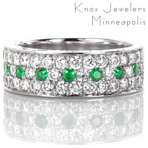 Design 3057 is paved with long rows of diamonds and gemstones. The micro pavé setting features two rows of stunning round brilliants with a single row of alternating diamonds and luscious green emeralds in between. The sides of this band are detailed with captivating hand engraved designs.