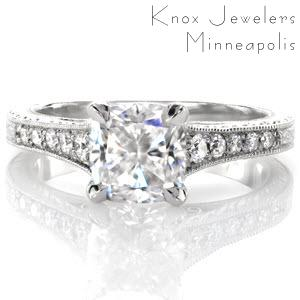 This antique inspired design is handcrafted in 14k white gold. A 1.00 carat cushion cut center stone is magnificently framed in a four prong setting. Tapered diamonds along the band is met by an elegant scroll engraved pattern. The side profile reveals hand-wrought filigree and a half-wheat engraved pattern.