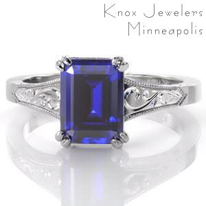 Gorgeous sapphire engagement ring in St. Petersburg. This luscious blue emerald cut sapphire is featured in an antique engagement ring style with hand engraved scroll patterns on the top and sides of the band. The sides of this unique engagement ring also feature delicate, hand formed filigree curls for vintage appeal.