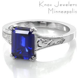 Sapphire engagement ring in Tulsa features a custom design with hand engraved patterns and hand wrought filigree curls. This antique engagement ring style inspiration is crowned with a stunning emerald cut blue sapphire.