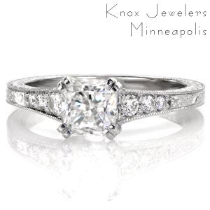 Four pairs of double prongs exquisitely hold a 1.00 carat radiant cut center stone. Tapered diamonds along the band is met by an elegant scroll engraved pattern. The prongs showcase the side profile of the center diamond for a picturesque view. Full wheat engraving adorn the sides for an antique appeal.