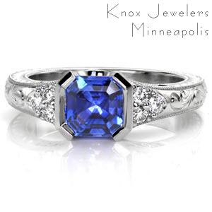 Kimberly's Dream is a lavish antique inspired ring displaying a rich asscher-cut blue sapphire in a half-bezel setting. This design features vintage inspired details including hand engraving, milgrain, and filigree. The cluster of three diamonds on either side of the center adds brilliance to its white gold mounting.