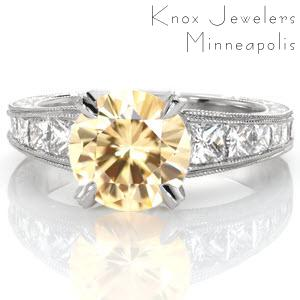 Showcasing an extraordinary 2.39 carat round yellow sapphire, design 3097 is the definition of luxury. This platinum setting's elegant bead-set diamond prong join with a tapering band featuring channel set princess cut diamonds, mil-grain edges and scroll hand engraving.