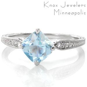 This stunning antique inspired design features a magnificent kite-set cushion cut aquamarine. A single round brilliant diamond accents the top of the ornately hand engraved band. The intricate details of milgrain and engraved patterns makes this ring remarkably gorgeous.