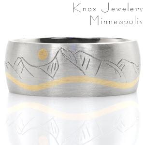This magnificent band captures the scenic view of of the Mission Mountains located in northern Montana. Handcrafted in platinum, the silhouette of the sun and the undulating movement of the Swan River are accented in 18k yellow gold for a dramatic affect.