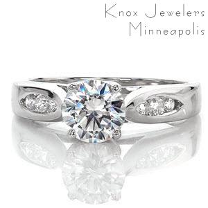 This contemporary ring is awe inspiring and uses minimal details to put all the focus on the 1.00 carat round brilliant cut center diamond. The elegantly swooping shoulders of the cathedral setting are made delicate by the open windows of the side profile. The top of the band has two pockets of channel set diamonds.