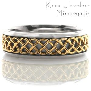 Interwoven strands of yellow gold creates a distinct Celtic pattern down the center of this eternity band. The white gold background has a sandblasted finish giving contrast and dimension to the polished Celtic pattern. Beveled edges frame the design and provides a comfortable fit.