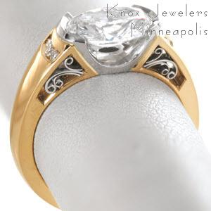 Beautiful two tone oval engagement ring in Los Angeles features a yellow gold band with a platinum half bezel center setting. The band is adorned with channel set diamonds and hand formed, platinum filigree curls.