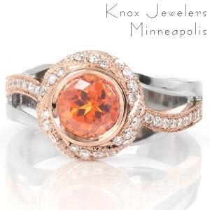 Design 3227 features a fiery orange 1.00 carat sapphire in a woven halo. The warm peachy hues of the rose gold halo and band perfectly compliment the center gem. The split shank of rose and white gold adds movement and dimension that flow with the halo. White diamonds adorn the halo and rose gold portion of the band.