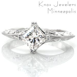 Design 3228 is a mesmerizing contrast of angles and curves. The crisp lines of the kite set princess cut center diamond are mirrored in the knife edged band style. The pockets of hand wrought filigree curls and the carefully hand carved, scroll pattern relief engraving add a graceful vintage appeal.