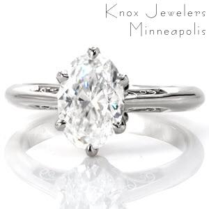 This stunning antique inspired engagement ring design features a 1.50 carat oval center stone in a six prong setting. The elegant band tapers at the top to seamlessly blend with the delicate petals adorning the base of the center stone. Graceful, hand crafted filigree curls give this piece vintage appeal.