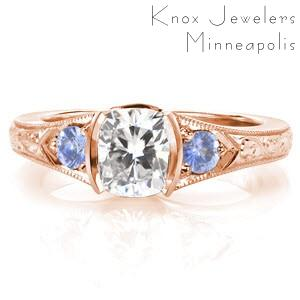 Rose gold engagement ring in Oakland with cushion cut center stone, blue sapphire side stones and scroll hand engraving.