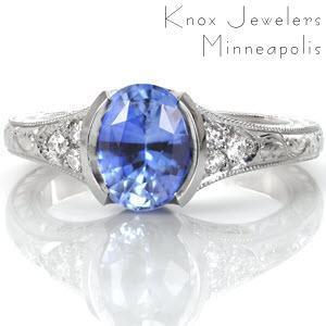 Design 3236 is shown with a 1.80 carat, oval cut, pale blue sapphire in a half bezel setting. The elongation of the center stone is accentuated by the flare of the band. This antique inspired engagement ring design is adorned with graceful hand formed filigree curls and elegant hand engraving.