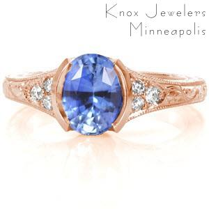 Des Moines custom rose gold engagement ring with an oval cut cornflower blue sapphire held in a half bezel setting with a hand engraved band.