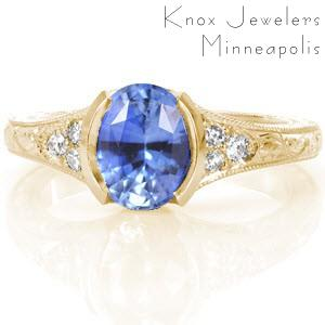 Providence custom engagement ring with an oval cut cornflower blue sapphire held in a half bezel setting with a hand engraved band.