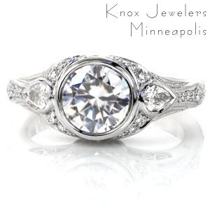 Crafted in Platinum, the Sylvia design has a full bezel center diamond with two pear cuts on each side. As the full flaired band tapers down, fine details of milgrain and round diamonds graduating in size adorn the band. Hand formed filigree curls are tucked under two grand swirls creating a great profile look.