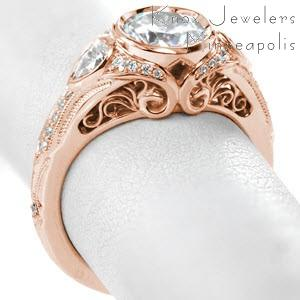 Portland rose gold engagement ring with filigree, pear cut side diamonds and full bezel round center stone.
