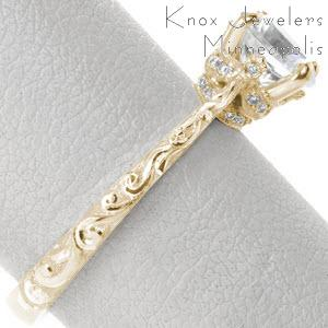 Yellow gold antique engagement ring in Denver features stunning relief style hand engraving on the band with a crown-like basket under the center stone. This regal center setting is adorned with micro pave diamonds.