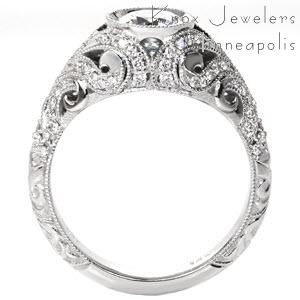 Beautiful art deco engagement ring in Raleigh is a delight of hand carved relief engraving and diamonds in swirl patterns around the bezel set center diamond.