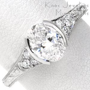 Antique engagement ring in Boston with half bezel oval center stone, hand engraving, and filigree.